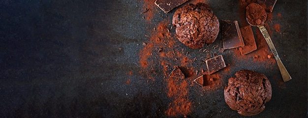 Шоколадный кекс на темной поверхности. вид сверху. баннер. плоская планировка Premium Фотографии