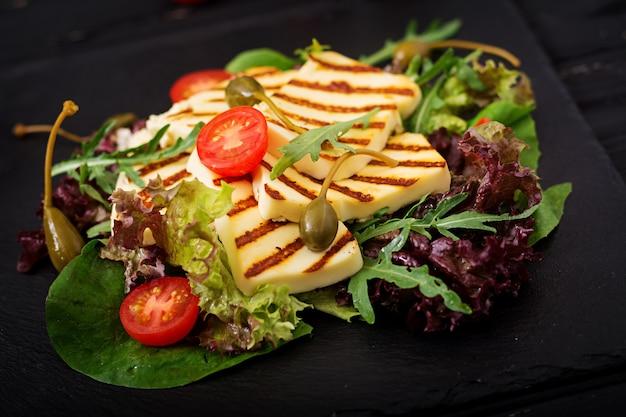 Свежий салат с жареным сыром, помидорами, каперсами, листьями салата и рукколой. Premium Фотографии