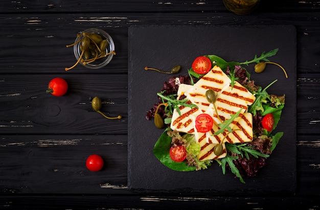 Свежий салат с жареным сыром, помидорами, каперсами, листьями салата и рукколой. квартира лежала. вид сверху Premium Фотографии