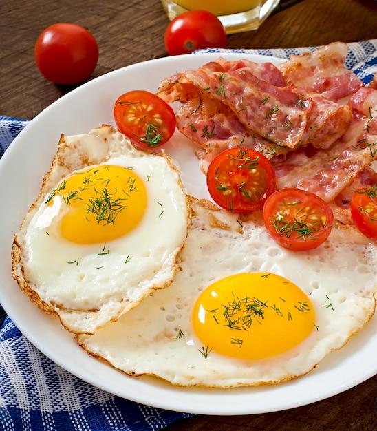 木製の素朴なスタイルのトースト、卵、ベーコン、野菜のイングリッシュブレックファースト Premium写真