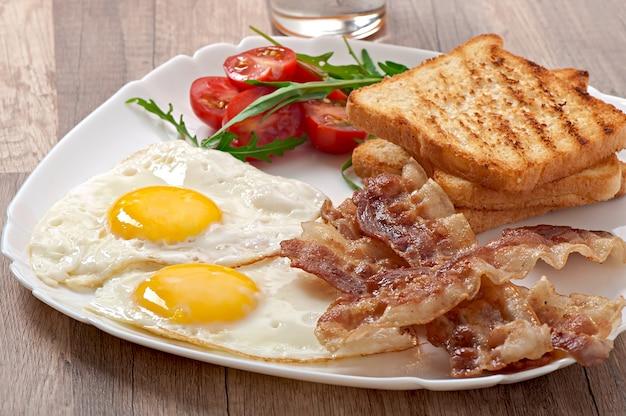イングリッシュブレックファースト-トースト、卵、ベーコン、野菜 Premium写真