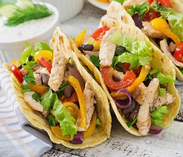 チキン、ピーマン、黒豆、新鮮な野菜とメキシコのタコス Premium写真