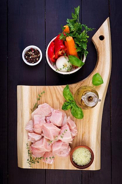 ハーブとスパイスを木製のまな板に生の鶏の胸肉の切り身。上面図 無料写真