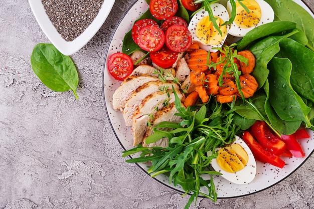 Тарелка с кето диетическое питание. помидоры черри, куриная грудка, яйца, морковь, салат с рукколой и шпинатом. кето обед. вид сверху Бесплатные Фотографии