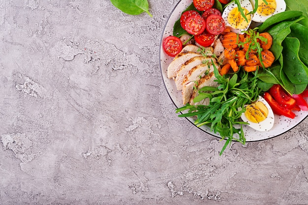 ケトダイエット食品のプレート。チェリートマト、鶏の胸肉、卵、ニンジン、ルッコラとほうれん草のサラダ。ケトランチ。上面図 無料写真