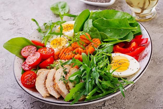 Тарелка с кето диетическое питание. помидоры черри, куриная грудка, яйца, морковь, салат с рукколой и шпинатом. кето обед Бесплатные Фотографии