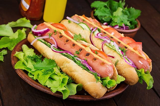 Хот-дог с колбасой, огурцом, помидорами и листьями салата на темный деревянный стол. летний хот-дог. Бесплатные Фотографии