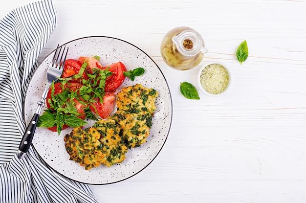 Запеченный стейк нарезанного куриного филе со шпинатом и гарниром из салата из помидоров. европейская кухня диетическое питание вид сверху Бесплатные Фотографии