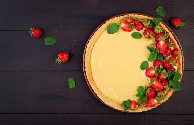 暗いテーブルにミントの葉で飾られたイチゴとホイップクリームのタルト。上面図 無料写真
