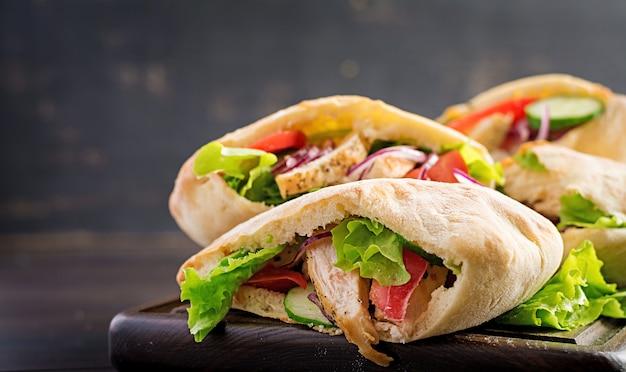 Пита, фаршированная курицей, помидорами и листьями салата на деревянный стол. ближневосточная кухня. Бесплатные Фотографии