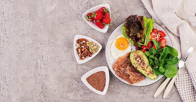 ケトダイエット食品のプレート。目玉焼き、ベーコン、アボカド、ルッコラ、イチゴ。ケト朝食。上面図 無料写真