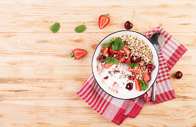 Здоровый завтрак - мюсли, клубника, вишня, орехи и йогурт в миску на деревянном столе. вегетарианская концепция еды. вид сверху Бесплатные Фотографии
