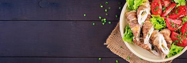 チーズとほうれん草を詰めたおいしいチキンロールはベーコンのストリップに包まれています。上面図 無料写真