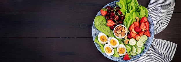 Тарелка с палео диетическим питанием. вареные яйца, авокадо, огурец, орехи, вишня и клубника. палео завтрак. вид сверху Бесплатные Фотографии