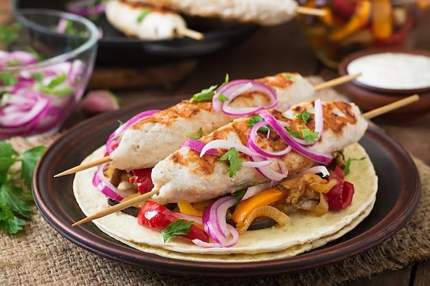 チキン、グリル野菜、赤玉ねぎとメキシコのタコス。 Premium写真