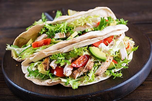 鶏肉のグリル、アボカド、トマト、キュウリ、レタスのピタパンサンドイッチを木製のテーブルで提供しています 無料写真