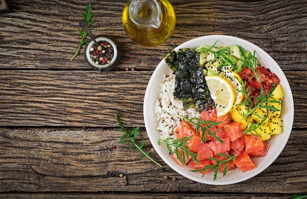 Тушеная рыба из гавайского лосося с рисом, авокадо, манго, помидорами, кунжутом и морскими водорослями. Premium Фотографии