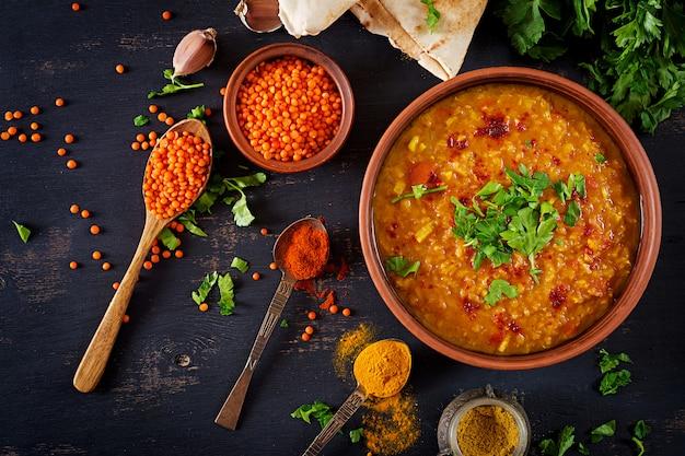 伝統的なインドのスープレンズ豆。ボウル、スパイス、ハーブ、素朴な黒い木製のテーブルでインドのダルスパイシーなカレー 無料写真