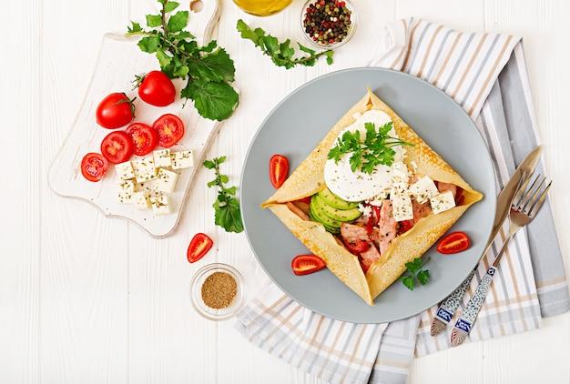 Французская кухня. завтрак, обед, закуски. блинчики с яйцом пашот, сыр фета, жареная ветчина, авокадо и помидоры на белом столе. вид сверху Бесплатные Фотографии