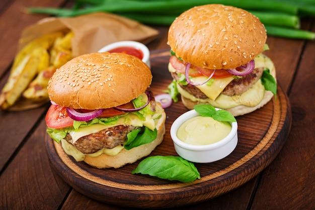 大きなサンドイッチ-ハンバーガーとジューシーなビーフハンバーガー、チーズ、トマト、木製のテーブルに赤玉ねぎ 無料写真