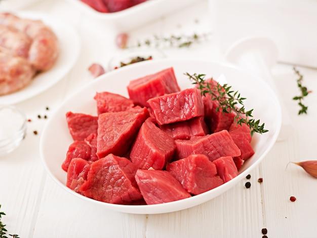 みじん切りの生肉。肉挽き器を用いて肉を準備するプロセス。自家製ソーセージ。牛ひき肉。 無料写真