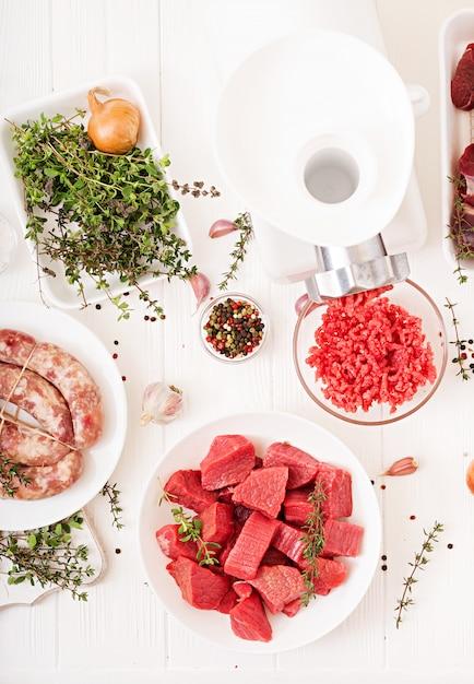 みじん切りの生肉。肉挽き器を用いて肉を準備するプロセス。自家製ソーセージ。牛ひき肉。上面図 無料写真