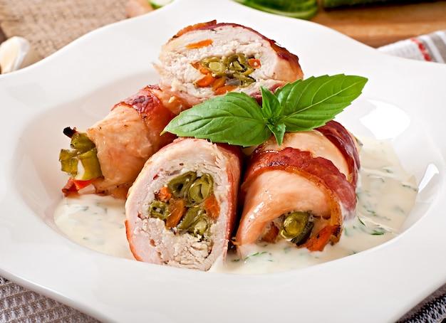 緑色の豆とにんじんをベーコンに包んだおいしいチキンロール 無料写真