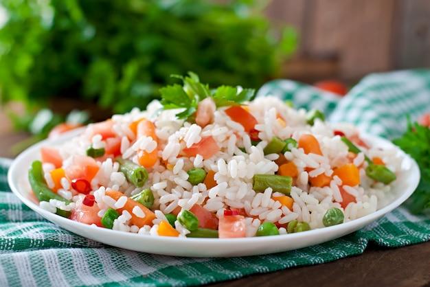 Аппетитный здоровый рис с овощами в белой плите на деревянном столе. Бесплатные Фотографии