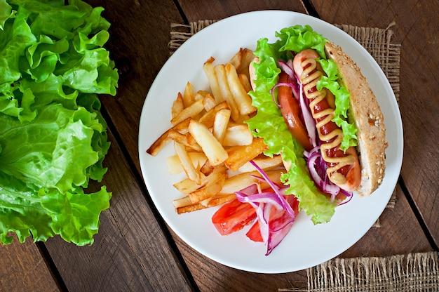 ケチャップマスタードとレタスの木製のテーブルのホットドッグ。 無料写真