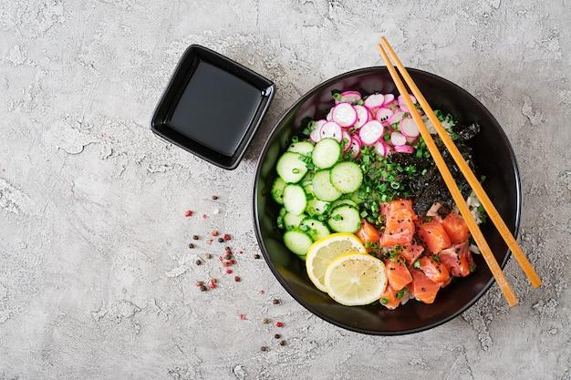 Тушеная рыба из гавайского лосося с рисом, редькой, огурцом, помидорами, кунжутом и морскими водорослями. чаша будды. диетическое питание. вид сверху. квартира лежала. Бесплатные Фотографии