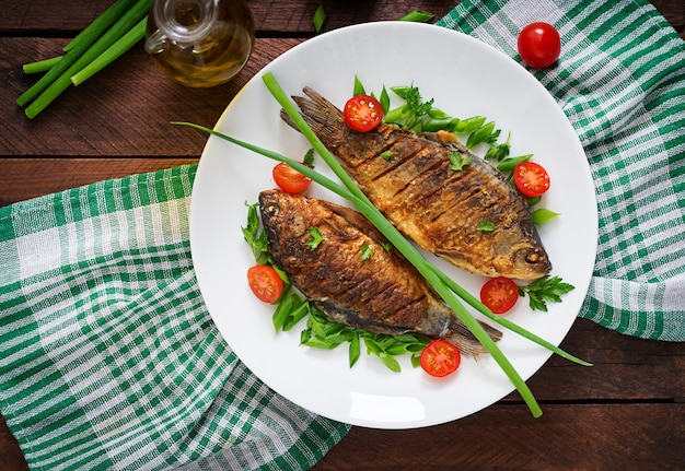 Зажаренный салат карпа и свежего овоща рыб на деревянном столе. квартира лежала. вид сверху Бесплатные Фотографии