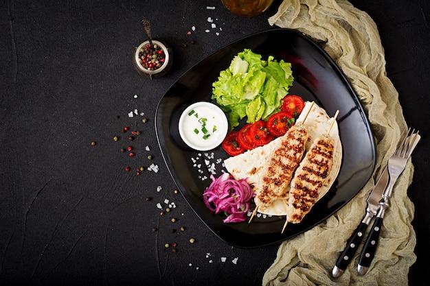 Фарш из люля кебаб на гриле, индейка (курица) со свежими овощами. вид сверху Бесплатные Фотографии