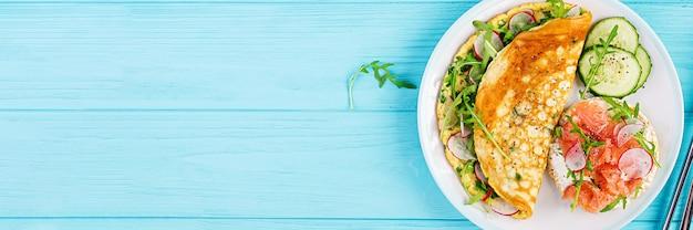 朝ごはん。大根、緑のルッコラと白い皿にサーモンのサンドイッチのオムレツ。フリッタータ-イタリアのオムレツ。上面図 無料写真