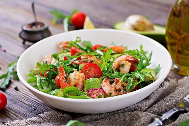 エビ、トマト、アボカド、ルッコラの木製の背景に新鮮なサラダボウルをクローズアップ。 Premium写真
