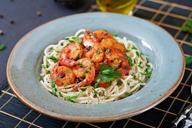 エビ、トマト、パセリのみじん切りとパスタスパゲッティ。健康食品。イタリア料理 Premium写真