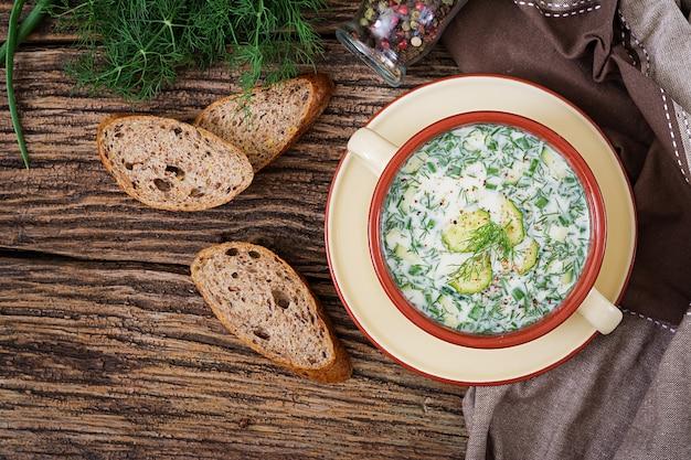 卵、きゅうり、木製のテーブルの上のディルと夏ヨーグルト冷たいスープ。オクロシカ Premium写真