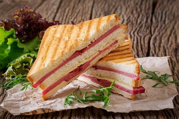 クラブサンドイッチ - 木製の背景にハムとチーズのパニーニ。ピクニックフード Premium写真