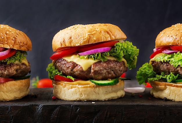 牛肉のハンバーガーと暗い背景に新鮮な野菜のハンバーガー。おいしい食べ物 Premium写真
