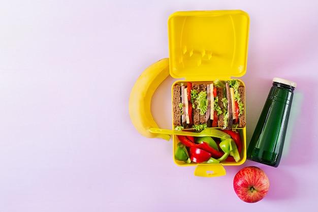 ビーフサンドイッチと新鮮な野菜、ボトル入り飲料水、ピンクの背景の果物と健康的な学校のお弁当箱。 Premium写真