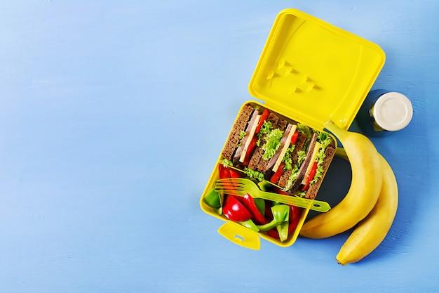 ビーフサンドイッチと新鮮な野菜、水のボトルと青の背景にフルーツの健康的な学校のお弁当箱。 Premium写真
