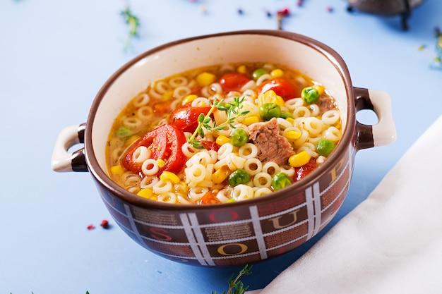 青いテーブルの上のボウルに小さなパスタ、野菜、肉の部分のスープ。 Premium写真