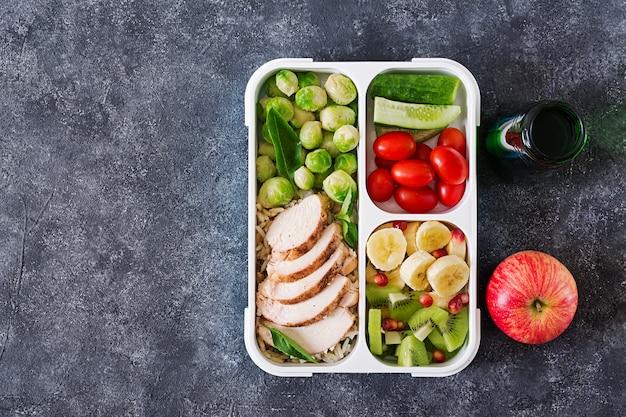 鶏ムネ肉、米、芽キャベツ、野菜、果物の入った健康的なグリーンミールの準備容器 Premium写真