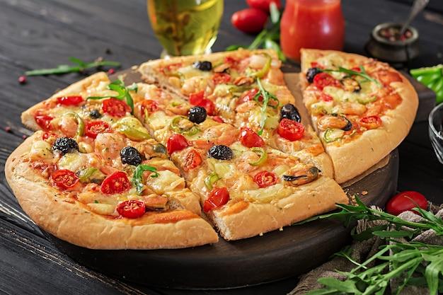 黒の木製テーブルの上のおいしいシーフードエビとムール貝のピザ。 Premium写真