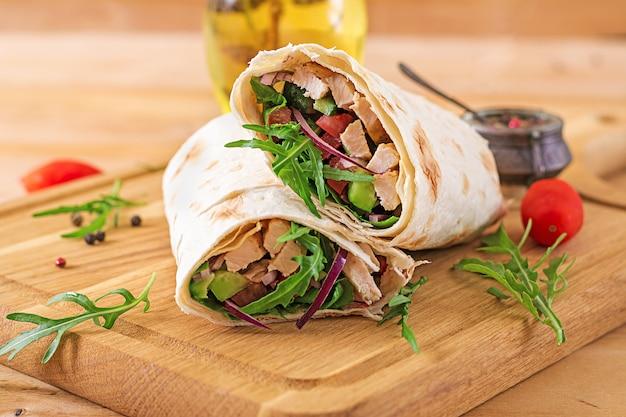 トルティーヤはチキンと野菜の木製の背景でラップします。 Premium写真