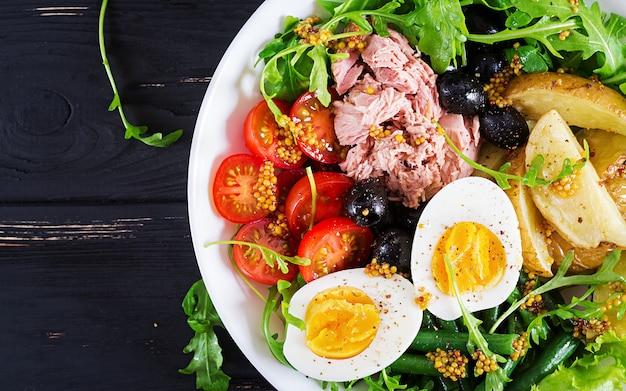 マグロ、インゲン、トマト、卵、ジャガイモ、ブラックオリーブのテーブルの上にボウルに健康的なボリュームのあるサラダ。 Premium写真