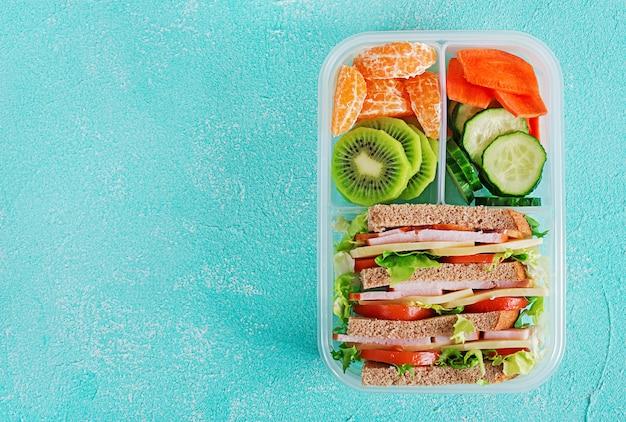 Коробка школьного обеда с бутербродом, овощами, водой и фруктами на столе. Premium Фотографии