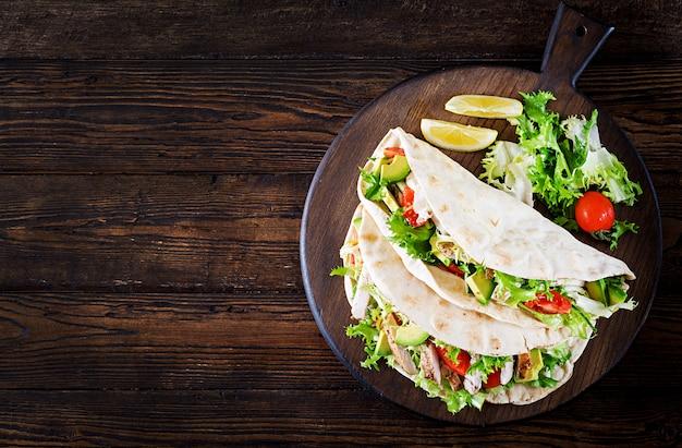 チキンのグリル、アボカド、トマト、キュウリ、レタスのピタパンサンドイッチ Premium写真
