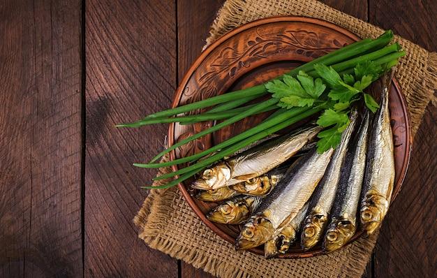 Копченая килька и зеленый лук на разделочной доске Premium Фотографии