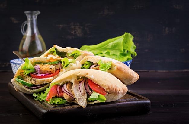 Пита фаршированная курицей, помидорами и листьями салата на деревянной, ближневосточной кухне. Premium Фотографии