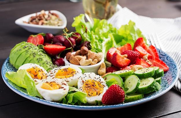 Тарелка с палео диетическим питанием, вареные яйца, авокадо, огурцы, орехи, вишня и клубника, палео завтрак. Premium Фотографии